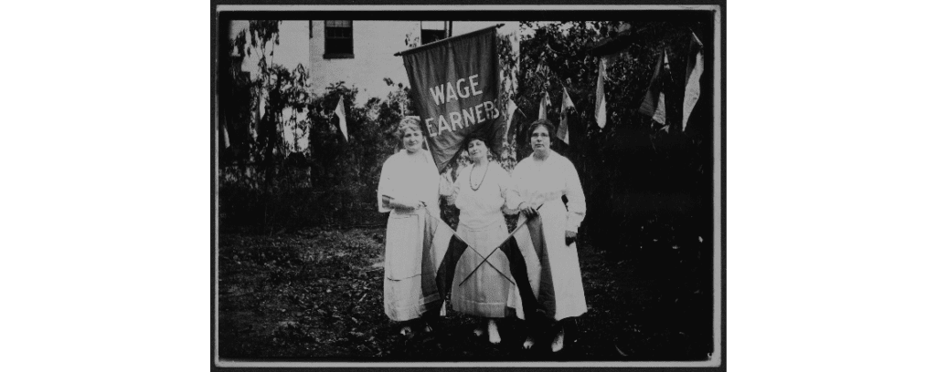 3 women hold a wage earners banner and two suffrage movement flags