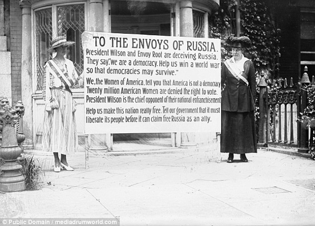 Wome suffragists hold a sign telling Russian envoys that America is not a democracy when twenty million American Women are denied the vote. This is to call the hypocrisy of a nation fighting for democracy abroad